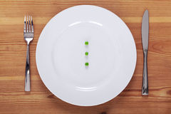 Peas on a white plate Royalty Free Stock Images