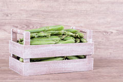 Peas in wooden box Stock Photos