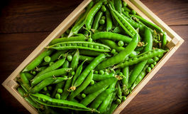 Peas in wooden box. On dark wooden table Stock Photography