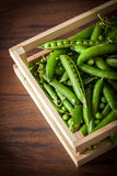 Peas in wooden box. On wooden table Stock Image