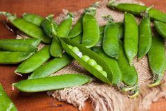 Peas on wooden desk with a pearl. On linen napkin Stock Photo