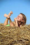 Peasant girl resting in haystack Stock Photography
