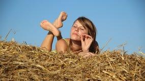 Peasant girl resting in haystack Stock Photos