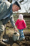 Peasant in his kitchen garden. An old peasant teaching his little granddaughter to work in the kitchen garden Stock Image