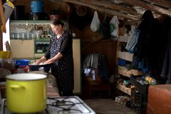 Peasant kitchen in Romania. An elderly woman who makes food in a traditional peasant kitchen in Romania, Salaj Area royalty free stock photo
