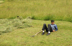 Peasant resting on a grass field Stock Photo