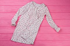 Peasant style girls` nightgown. On pink wooden background. Adorable ruffles and flowers. Kids sleepwear Royalty Free Stock Images