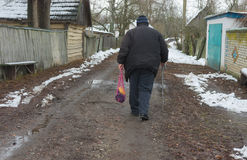 Peasant with walking stick goes on an empty street of rural village Pidstavky, Sumskaya oblast, Ukraine Royalty Free Stock Image