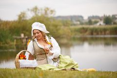 A peasant woman with a basket sits by the river Royalty Free Stock Photo
