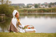 A peasant woman with a basket sits by the river Stock Photos