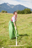 Peasant woman in dirndl when working with a rake. Royalty Free Stock Photos