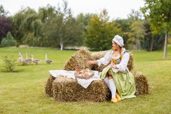 The peasant woman sits on the hay. Hike to a picnic Royalty Free Stock Photo