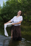 Peasant woman washes clothes in the river Royalty Free Stock Image