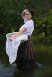 Peasant woman washes clothes in the river Royalty Free Stock Photography