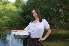 Peasant woman washes clothes in the river Royalty Free Stock Images