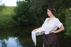 Peasant woman washes clothes in the river Stock Images