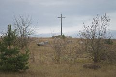 Peasant wooden cross on the mountain near the river bank, lake. Stock Photography