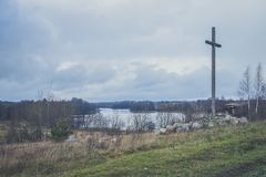 Peasant wooden cross on the mountain near the river bank, lake. Royalty Free Stock Images