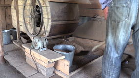 Peasant worker scoop sifted grain with shovel to metal bucket stock footage