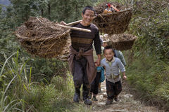 Peasants carrying a heavy load on their shoulders Stock Images