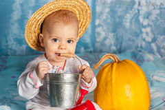 Peasants child in a straw hat holding a small aluminum bucket an. D orange pumpkin Stock Photos