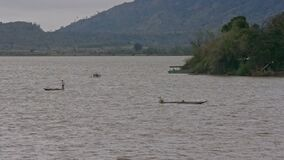 Peasants Fish in Long Canoes on Lake under Rain. Vietnamese peasants squat and fish in long wooden canoes on lake against distant hills under rainy weather stock video footage