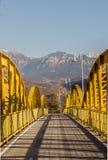 Peatón y puente de acero amarillo del ciclo con las montañas en Fotografía de archivo