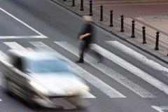 Peatón y un coche de conducción en el paso de cebra Foto de archivo