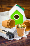 Peat pots, bird-house, seedlings and garden tools on wood background Stock Images