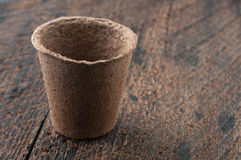 Peat Pots. One Peat Pots on is  wooden background Stock Photo