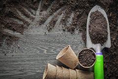Peat pots soil shovel on wooden board Stock Images