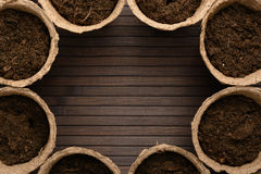 Peat pots with soil. On a wooden table royalty free stock images