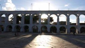 Peatones de Carioca con los rayos solares que hacen excursionismo los arcos coloniales del siglo XIX de Lapa, Rio de Janeiro, el  metrajes