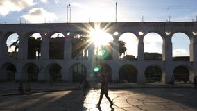 Peatones de Carioca con los rayos solares que hacen excursionismo los arcos coloniales del siglo XIX de Lapa, Rio de Janeiro, el  almacen de metraje de vídeo