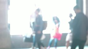 Peatones de Defocussed que caminan más allá de una pantalla brillante almacen de video