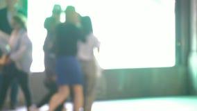 Peatones de Defocussed que caminan más allá de una pantalla brillante metrajes