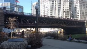 Peatones que caminan a lo largo del ` s Riverwalk céntrico de Chicago durante la primavera