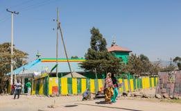 Peatones que caminan más allá de una iglesia colorida en un st del lado Foto de archivo libre de regalías