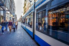 Peatones y tranvías en la calle ocupada de las compras del Leidsestraat en el centro de Amsterdam fotografía de archivo