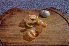 Peau d'oignon et les restes d'un oignon se reposant sur un hachoir en bois photos libres de droits