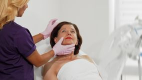Peau de examen de cosmetologist professionnel d'un patient féminin supérieur banque de vidéos