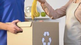 Peau de lancement de banane de femme au foyer dans la boîte pour les déchets organiques, recyclage des déchets banque de vidéos