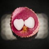 Peau de litchi avec l'agate en forme de coeur sur le noir Image libre de droits