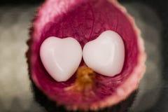 Peau de litchi avec l'agate en forme de coeur sur le noir Images stock