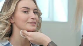 Peau de nettoyage d'artiste de maquillage sur le visage modèle Photo libre de droits