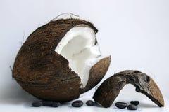 Peau de noix de coco et grains de café sur une fin blanche de plat  photographie stock libre de droits