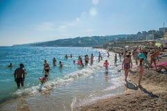 Pebble海滩的沐浴者有阳光的在背景中在卡西斯 库存图片