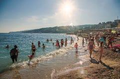 Pebble海滩的沐浴者有阳光的在背景中在卡西斯 免版税库存照片