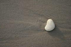 Pebble 1. White pebble on grey sand Stock Image