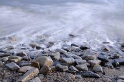 海洋在岩石Pebble海滩的水浪潮长的曝光  免版税库存照片